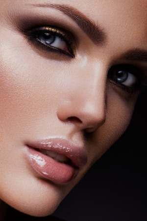 Close-up portrait of beautiful woman with bright make-up and hairstyle.