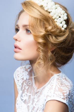 Glamour portrait de la belle fille modèle avec le maquillage et romantique ondulée coiffure. Mode surligneur brillant sur la peau, des lèvres brillantes sexy maquillage et sourcils sombres.
