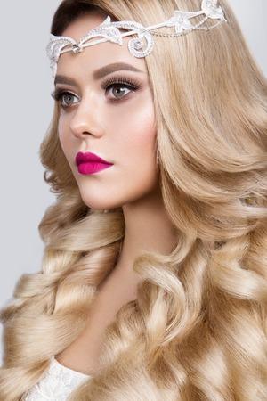 ojos azules: Modelo joven hermoso con los labios de color rosa y el pelo rizado