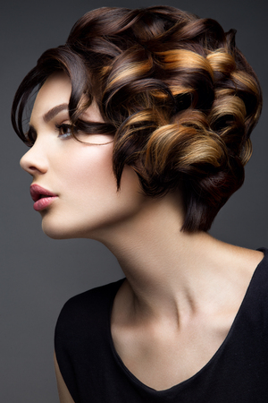 Retrato del encanto del modelo de muchacha hermosa con maquillaje y peinado ondulado romántico. Moda brillante en la piel, labios sexys brillo maquillaje y cejas oscuras.