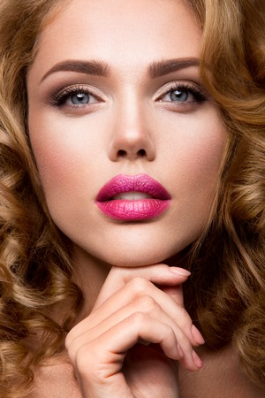 femme romantique: Glamour portrait de la belle fille modèle avec le maquillage et romantique ondulée coiffure. Mode surligneur brillant sur la peau, des lèvres brillantes sexy maquillage et sourcils sombres.