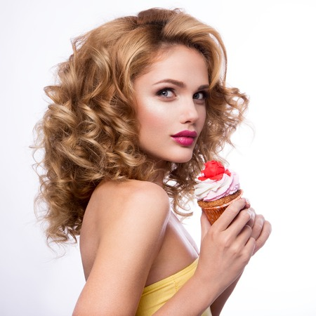 Beautiful fashion girl with bright make up, handing cupcake.