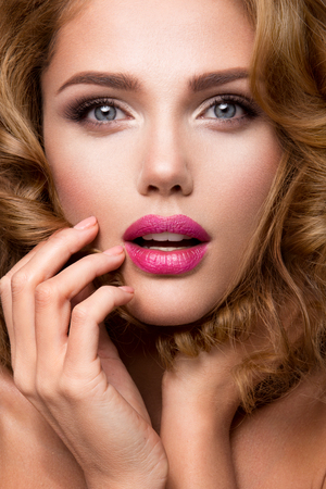 labios sexy: Retrato del encanto del modelo de muchacha hermosa con maquillaje y peinado ondulado romántico. Moda brillante en la piel, labios sexys brillo maquillaje y cejas oscuras. Foto de archivo
