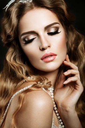 sexy glamour: Glamour portrait of beautiful girl model with makeup and romantic wavy hairstyle. Fashion shiny highlighter on skin, sexy gloss lips make-up and dark eyebrows. Stock Photo