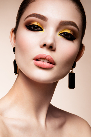 Glamour portrait of beautiful girl model with makeup. Fashion shiny highlighter on skin, sexy gloss lips make-up and dark eyebrows.