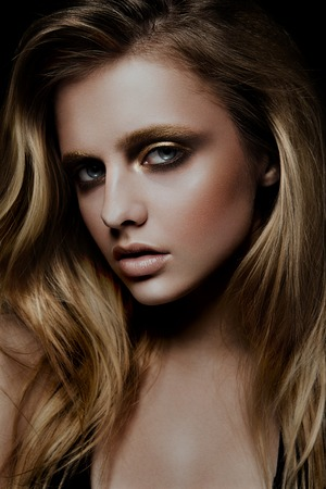 color model: Glamour portrait of beautiful girl model with makeup and romantic wavy hairstyle. Fashion shiny highlighter on skin, sexy gloss lips make-up and dark eyebrows. Stock Photo