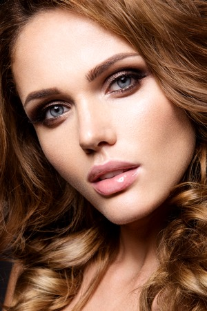 Close-up portrait of beautiful woman with bright make-up and curly hair