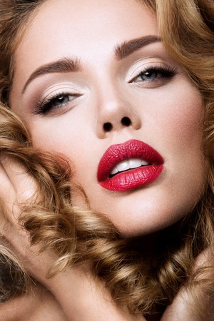 Glamour portrait of beautiful girl model with makeup and romantic wavy hairstyle. Fashion shiny highlighter on skin, sexy gloss lips make-up and dark eyebrows. Foto de archivo