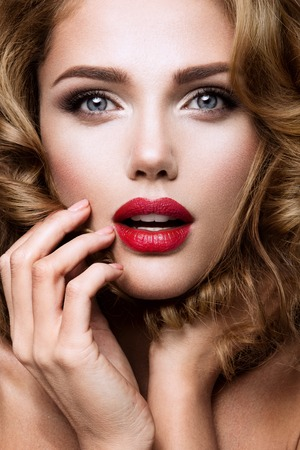 labios sensuales: Retrato del encanto del modelo de muchacha hermosa con maquillaje y peinado ondulado romántico. Moda brillante en la piel, labios sexys brillo maquillaje y cejas oscuras. Foto de archivo