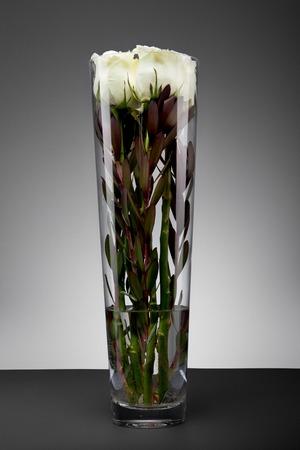 rosas blancas: Bouquet of pink roses in glass vase, jn a grey background Foto de archivo
