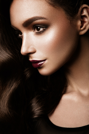 sexy fashion: Glamour portrait of beautiful woman model with fresh daily makeup and romantic wavy hairstyle. Fashion shiny highlighter on skin, sexy gloss lips make-up and dark eyebrows Stock Photo