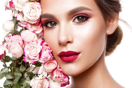 beautiful rose: Portrait of young beautiful woman with stylish make-up and colorful roses around her face