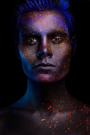 astral: Glowing neon makeup with dramatic look in his eyes. Creative body art on the theme of space and stars. Amazing close-up portrait glow in the dark makeup.