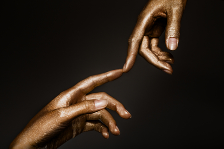 beautiful mans hands in golden paint on black background close up Stockfoto