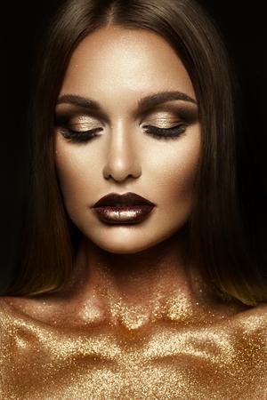 Ragazza di Beautyful con glitter oro sul viso e sul corpo