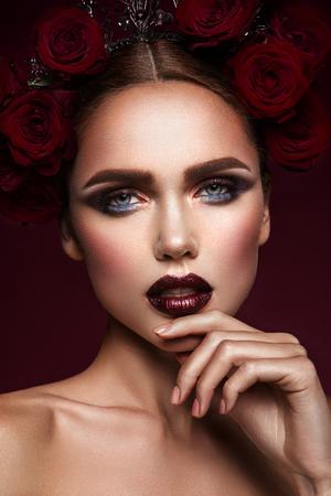 Close-up portret van mooie vrouw met donkere make-up en kapsel.