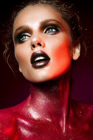Beautiful woman with red make up and glitter on the neck and hair