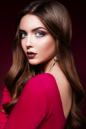 Woman in a red dress, with bright make up and beautiful hairstyle