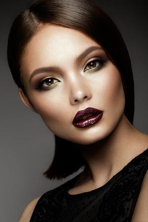 caras pintadas: Muchacha de Beautyful con brillante maquillaje y peinado hermoso Foto de archivo