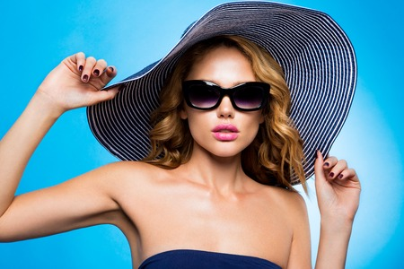 Beautiful young woman in elegant hat and sunglasses Stock Photo