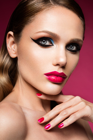 Beautiful young female face with bright fashion multicolored make-up photo