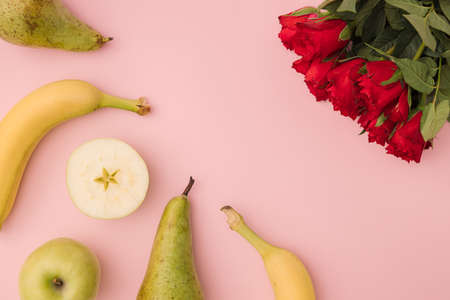 Creative layout made of summer tropical fruits and reds rouse on pink backround. Flat lay. Food concept.