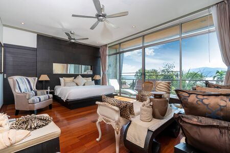 Bedroom with window glass door, ceiling fan and wooden flooring in pool villa, house, home, condo and apartment