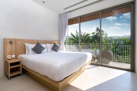 Interior design in villa, house, home, condo and apartment feature bedding, pillow, and television in bedroom with a view
