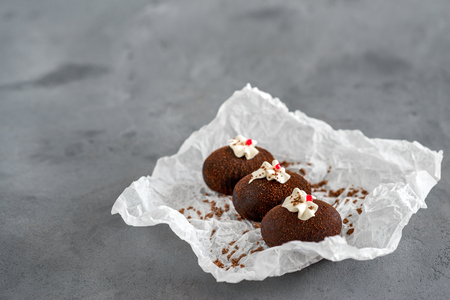 Cakes made of chocolate on a white transparent paper on a gray background. Cakes decorated with red jelly and delicate white cream.