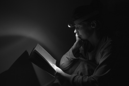 penury: Woman reading a book with the torch while electricity is off
