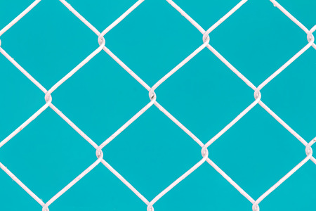 wire fence: White wire fence on green background Stock Photo