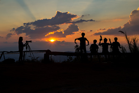 Photographers silhouetted before sun set photo