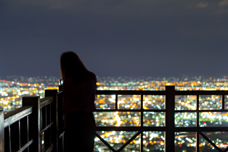 city light: Defocused Girl and city light from viewpoint Stock Photo