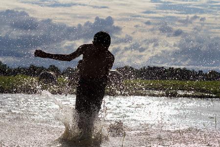farm duties: Boy running race silhouette on a swamp