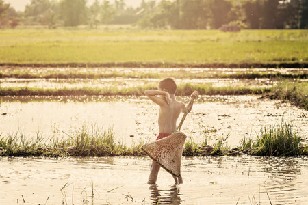 entrapment: Young agriculturist fishing in swamp by coop, Vintage style