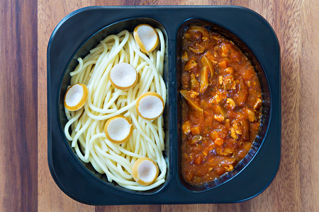 refrigerator with food: Spaghetti with red tomato sauce in a plastic box