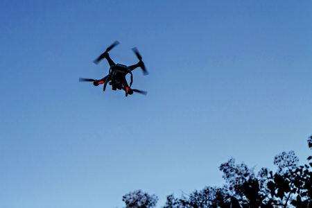 silhouetted: Drone with camera silhouetted in the sky