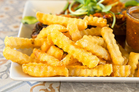 Tasty fried french fries on dish Standard-Bild