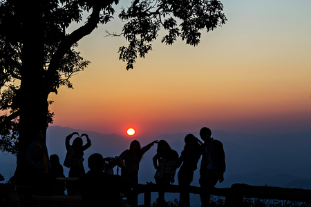 silhouetted: Peoples had happy motion, silhouetted with stunning sunset Stock Photo