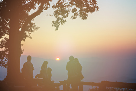 silhouetted: Tourist and big tree silhouetted with stunning sunset, vintage style