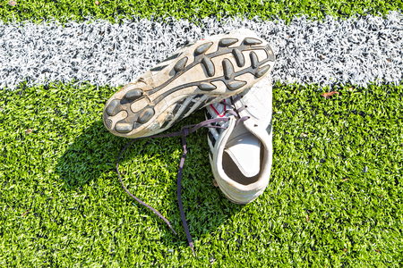 soccer shoes: Old soccer Shoes on artificial turf field with white marking line