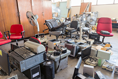 Gebrochene Bürostühle und Elektronik-Altgeräte im Lagerraum Standard-Bild - 55469450