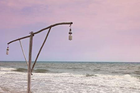 lamp on the pole: Lamp pole with the sea on evening time Stock Photo