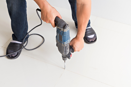 drill floor: Man hold electric drill on the floor