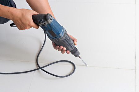 drill floor: Man hands hold electric drill on the floor