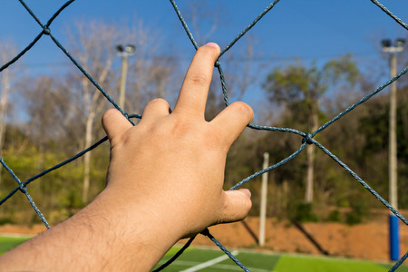grab: Hand grab the rope mesh fence Stock Photo