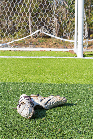 soccer shoes: Old soccer Shoes on artificial turf field with goal Stock Photo
