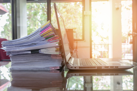 flare stack: laptop and document stack on office desk with sun flare