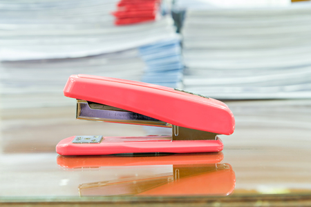 Stapler and business documents stack on table