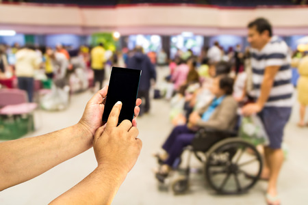 outpatient: Mobile phone in hand on out-patient department blurred background